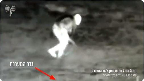 Picture from a video documenting a Palestinian terrorist armed with a rifle approaching the security fence (IDF Twitter account, December 17, 2019).