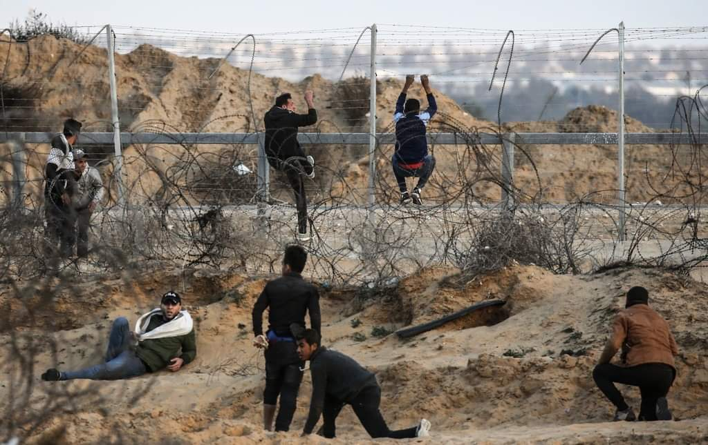 Palestinian rioters climb the security fence in eastern Khan Yunis (Palinfo Twitter account, December 19, 2019).