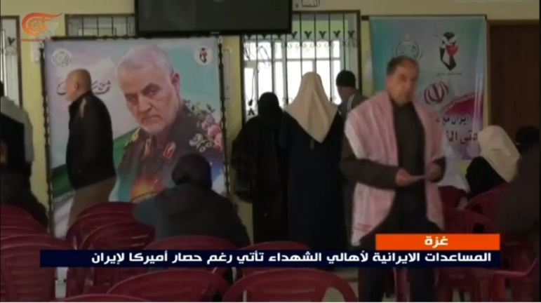 A picture of Qassem Soleimani with the Iranian Shaheed Foundation logo and the symbol of the Iranian flag, hung in the offices of the al-Ansar charitable association where checks were distributed to the families of shaheeds.
