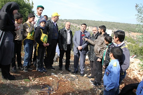 Sheikh Fouad Hanjoul, in charge of Hezbollah's Association for Municipal Activity in the first Lebanese region, south of the Litani River (center, holding microphone) (al-Manar). Standing next to him are leaders and scouts from Hezbollah's Imam al-Mahdi scouting organization. The scouts and their leaders planted trees in an event organized by the Jihad al-Bina and Green Without Borders in the village of Ayta al-Shab (Jihad al-Bina website, January 17, 2014).