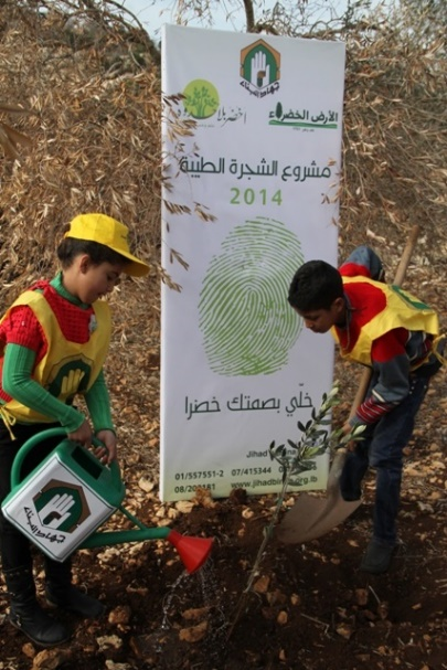 A Jihad-al Bina sign regarding a tree-planting project in the village of al-Dheere (near the Israeli border in the western sector of south Lebanon). Both the sign (top center) and the watering can bear the Jihad al-Bina logo. The Green Without Borders logo appears in the upper left-hand corner (Jihad al-Bina website, January 22, 2014).