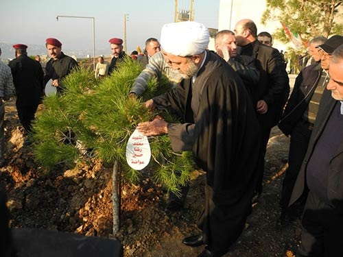 Sheikh Nabil Qawouq, deputy chairman of Hezbollah's executive council, plants trees in a joint Jihad al-Bina-Green Without Borders ceremony. The trees were planted to commemorate Hezbollah shaheeds Muhammad Rida Hussein Awada (right picture) and Hitham Fouad Dabaja (left picture) (Jihad al-Bina website, January 18, 2014).