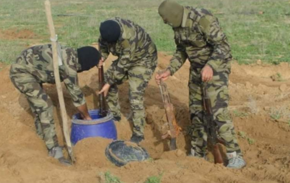 Popular Mobilization operatives removing a plastic container, inside which ISIS weapons were hidden (al-hashed.net, February 28, 2020)