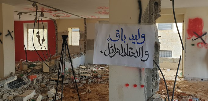 "The demolished house of Walid Hanatsha in the al-Tira neighborhood of Ramallah. The sign reads, ""Walid remains and the occupation passes"" (Palinfo Twitter account, March 5, 2020)."