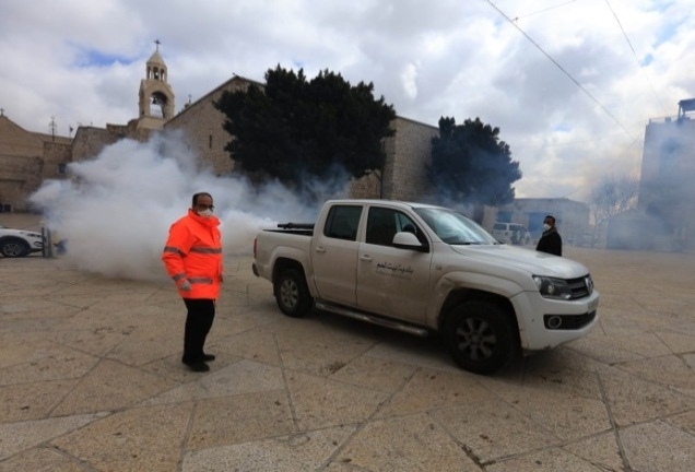 Employees of the Bethlehem city hall disinfect the area in front of the Church of the Nativity (Wafa,, March 7, 2020).