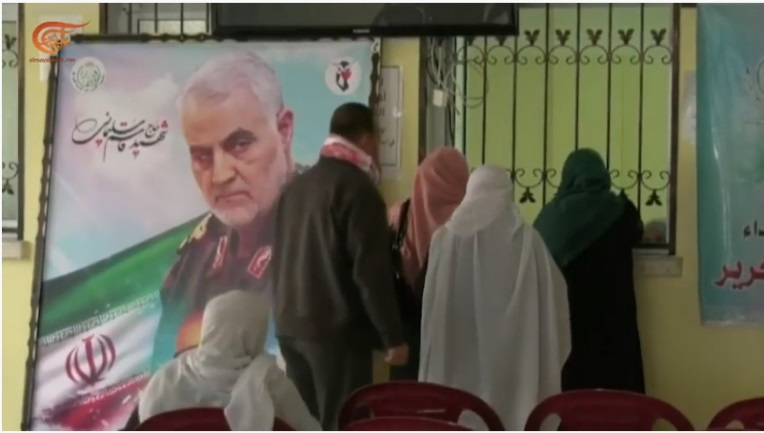 Photo of Qassem Soleimani, the Iranian flag and the emblem of the Palestinian Martyrs Foundation, which were posted in the offices of the Al-Ansar Charity Association in Gaza while distributing the vouchers to the representatives of the families of shaheeds (Facebook page of the Al-Ansar Charity Association, January 27, 2020)