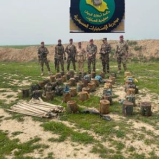 Iraqi soldiers near the explosives found in the searches.