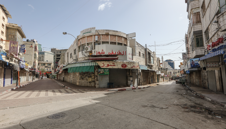 Empty streets and shuttered businesses in the wake of the measures recently declared by the Palestinian government. Right: The center of Ramallah (Wafa, March 23, 2020).