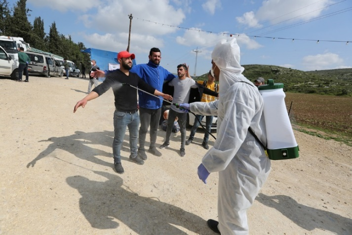 Palestinian medical teams at the Tarqumiya crossing disinfect Palestinian workers returning from Israel (Wafa, March 25, 2020).