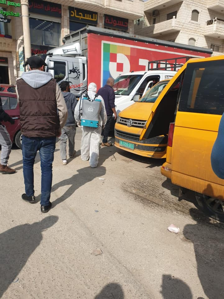 Fatah emergency committee operatives in the town of E'izariya disinfect taxis.