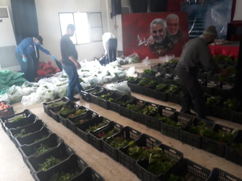 Gathering food for distribution to the needy in Abba, southern Lebanon (Rassed Network's Facebook page, March 26, 2020). Photos of Qassem Soleimani and Abu Mahdi al-Muhandis, killed along with him, can be seen in the background, as well as the photo of Hassan Nasrallah.