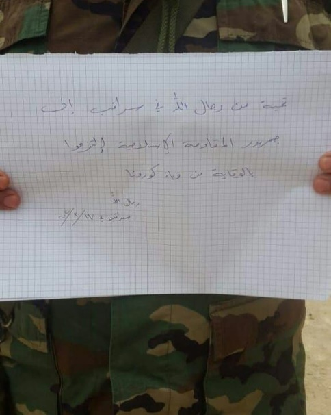 "Hezbollah fighter holding a sign: ""Greetings from the Men of Allah in Saraqeb [a town in the Idlib district in Syria] to the public of Islamic resistance. Please make sure to protect yourselves from COVID-19. Men of Allah, Saraqeb, March 17, 2020"" (Facebook, March 2020)."