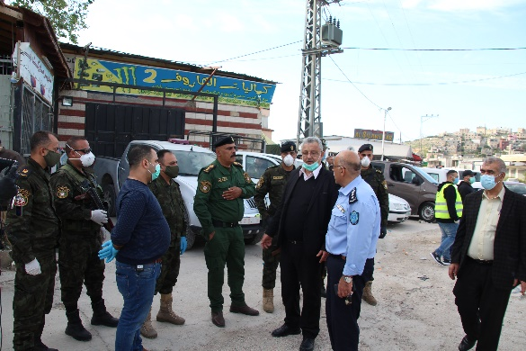 Issam Abu Bakr, governor of the Tulkarm district, visits the roadblocks in his district, accompanied by employees of the Palestinian ministry of health.