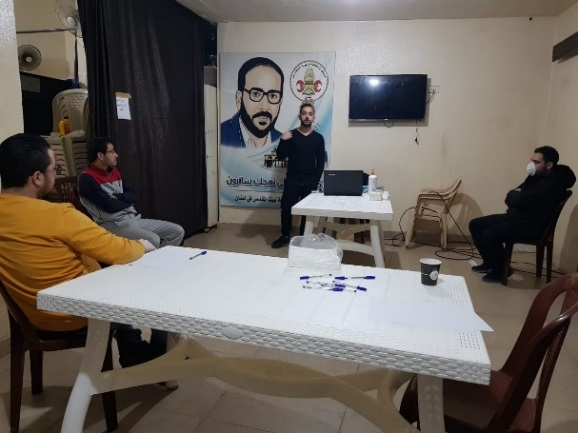 PIJ-led training workshop in the Shatila refugee camp on the fight against COVID-19 (Shababeek, March 26, 2020). A picture of PIJ founder Fathi Shiqaqi is seen in the background.