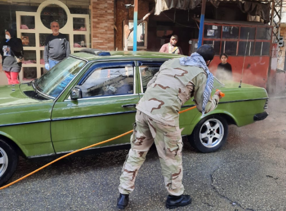 Members of the Joint Security Force disinfecting a vehicle at the entrance to the Ein al-Hilweh refugee camp (Al-Manar TV, March 21, 2020)