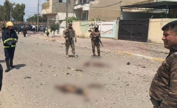 Iraqi security personnel standing near body parts of the suicide bomber (blurred in the original), close to the entrance to the building of the Intelligence and Counterterrorism Directorate in Kirkuk (azzaman@azzamannews, Twitter account of an international Arab daily operating from Iraq, April 28, 2020).