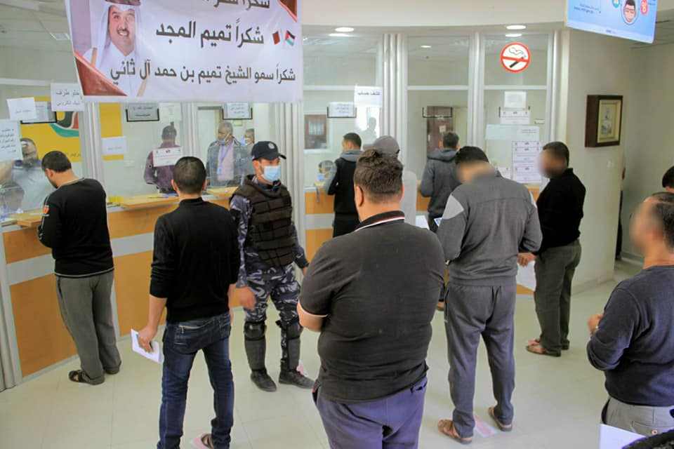Funds from Qatar distributed at post office bank branches, while people practice social distancing and operatives of Hamas' security forces supervise (Facebook page of Qatar's National Committee for the Reconstruction of Gaza, May 2, 2020).