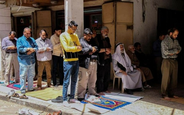 A group of vendors hold a public prayer on the sidewalk in a market (al-Majala, May 2, 2020).