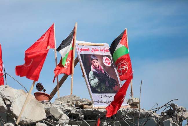 The ruins of the house of Qassem Shibli Barghouti with Palestinian flags hung on the roof and a picture of the terrorist with the caption,