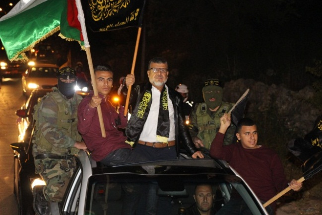 Senior PIJ figure Jumaa al-Thaya en route to the reception accompanied by two of his sons and two masked PIJ operatives wearing Jerusalem Brigades headbands.