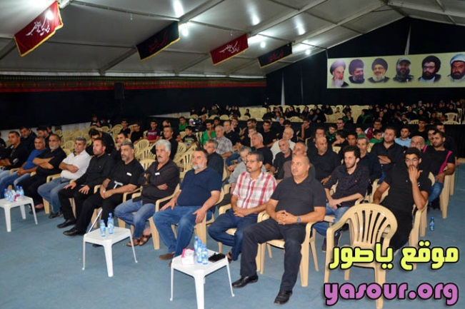 The audience at the ceremony where Jawad Nur al-Din made his speech (Ya Sour, September 23, 2017). Photos of Ayatollah Khomeini, Hassan Nasrallah, Imad Mughniyeh, Abbas Mussawi and other senior Hezbollah leaders are visible in the background.