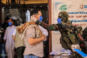 An operative of Hamas' military wing helps a man put on a mask (Twitter account of photojournalist Muhammad al-Masri, May 22, 2020).