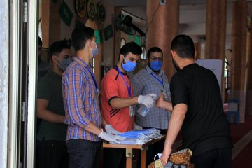 Distributing masks and sanitizing the hands of worshippers at mosque entrances (Twitter account of the ministry of the interior in the Gaza Strip, May 22, 2020).