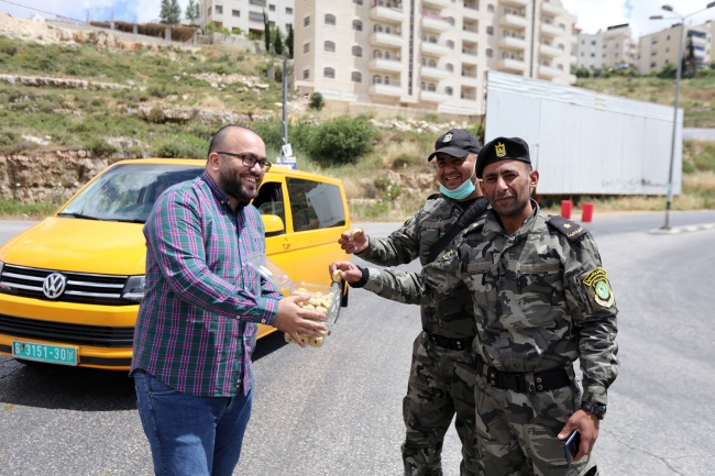 Local residents distribute pastries to the Palestinian security forces for Eid al-Fitr (Wafa, May 24, 2020).