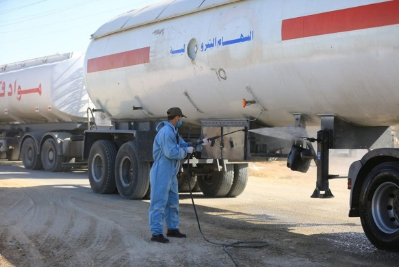 Operatives of the national security forces disinfect gas and diesel fuel containers from Egypt that entered the Gaza Strip through the Rafah Crossing (Facebook page of the ministry of the interior in Gaza, June 17, 2020).