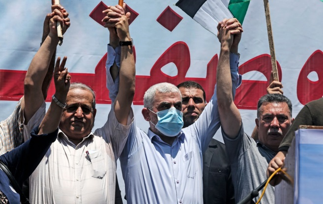 Yahya al-Sinwar (mask) holds the raised hand of senior Fatah figure Ahmed Hilles (right) in a show of unity (Shehab Twitter account, July 1, 2020).