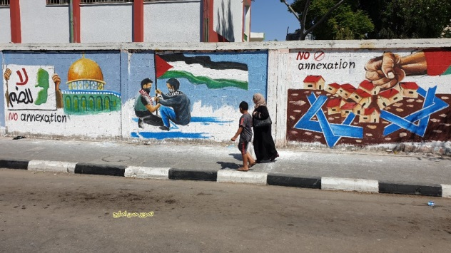 "Mural in Rafah. From left to right, al-Aqsa mosque with a sign reading ""No annexation,"" mask-wearing Palestinians plant a Palestinian flag on an Israeli flag, a fist smashes houses representing the Israeli communities in Judea and Samaria and ""No annexation"" (Twitter account of journalist Hassan Twitter account of journalist Hassan Aslih, July 1, 2020)."