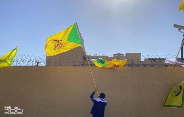 Kataeb Hezbollah's flag waving above the US Embassy wall (Baghdad al-Youm, December 31, 2019).