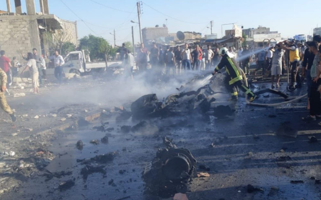 A firefighter and a civil defense operative spraying water on the wreckage of the car bomb (Nagi N. Najjar@NagiNajjar Twitter account, affiliated with the Turkish-sponsored rebel organizations, July 19, 2020).