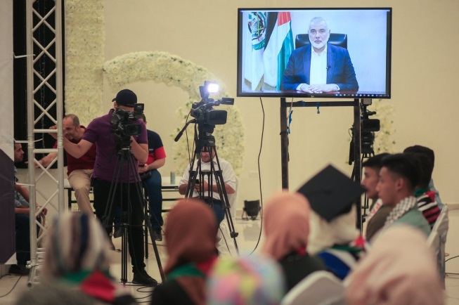 Ceremony held for children of shaheeds who passed their matriculation exams. Left: Isma'il Haniyeh gives a recorded speech (Hamas website, July 22, 2020).