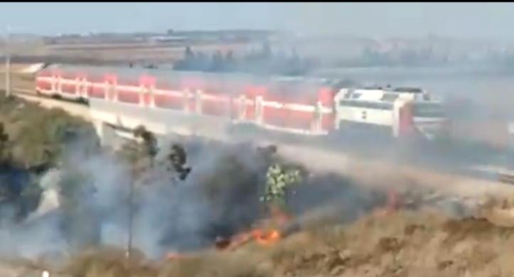 A fire near the train tracks in the western Negev as a train passes (Twitter account of Almog Boker, August 26, 2020).