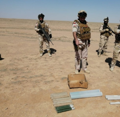 An Iraqi army officer and soldiers near some of the captured weapons.