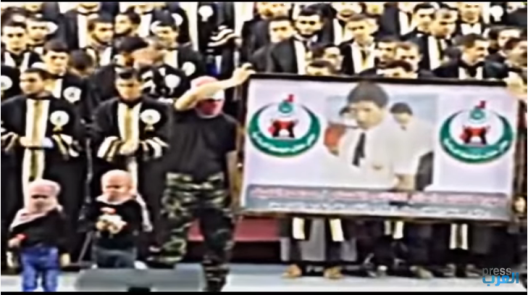 Masked Palestinians, apparently Hamas operatives, and two children holding toy guns went on stage during a ceremony honoring outstanding IUG students. The masked men held a banner with a picture of Muhammad Deif, head of Hamas' military wing, who was seriously injured in an attempted IDF targeted killing attack. Muhammad Deif was an IUG graduate and during his studies was an activist in Hamas' student cell (Islamic Bloc). The picture on the banner is apparently from his days as a student (YouTube, May 11, 2015).