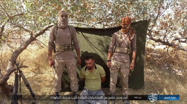 Two ISIS operatives (the one on the left holding a knife) standing behind an Iraqi intelligence operative before executing him (Telegram, September 25, 2020)