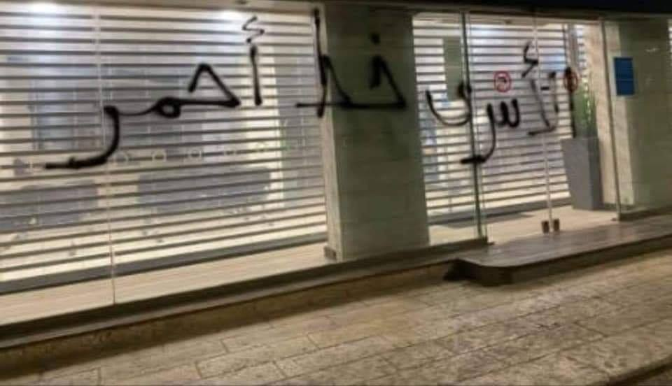 "Graffiti sprayed on the front windows of the Arab Bank in al-Bireh. The Arabic reads, ""The prisoners are a red line"" (Facebook page of RamallahMix, September 19, 2020)."