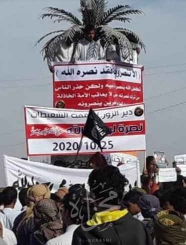 "ISIS flag waved during a demonstration in the Deir ez-Zor region. The main sign reads, ""It wasn't you who overcame him [i.e., the infidel], but Allah who brought [you] the victory. Allah promised victory to His prophet […], but He [Allah] warned people not to quit supporting him [i.e., the prophet], otherwise He [Allah] will punish the failing nation [for that] and replace it with others who will overcome them"" . The second sign reads, ""Deir ez-Zor / the protest of Al-Shueitat – support of [the prophet of] Allah – October 25, 2020 (Telegram, October 25, 2020)."