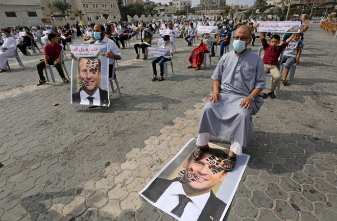 A demonstrator sits with his feet on a picture of French President Macron at a demonstration in Khan Yunis (Twitter account of photojournalist Ashraf Abu Amra, October 30 2020).
