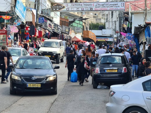 "Israeli Arabs shop in the market in Barta'a (Facebook page of the ""al-Jalameh roadblock from Jenin,"" November 14, 2020. The cars with yellow license plates are Israeli."