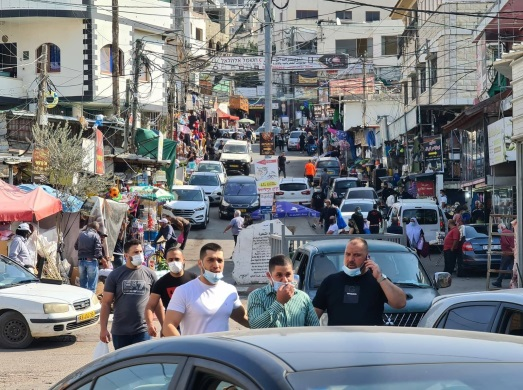 """Israeli Arabs shop in the market in Barta'a (Facebook page of the """"al-Jalameh roadblock from Jenin,"""" November 14, 2020. The cars with yellow license plates are Israeli."""