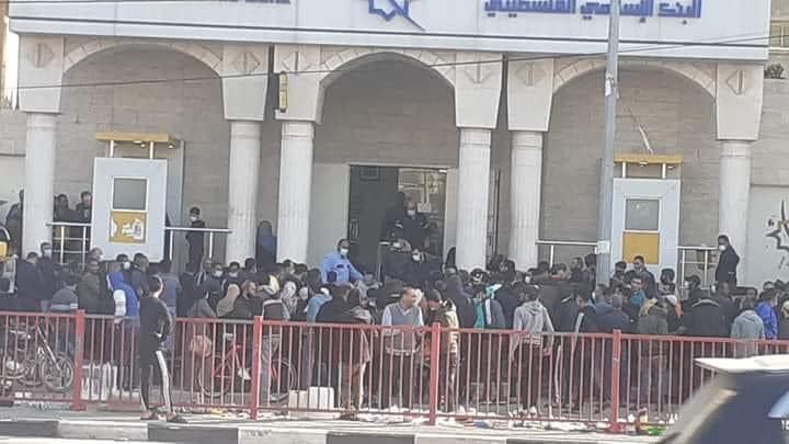 Palestinians crowding at the entrance of the Palestinian Islamic Bank in the Nuseirat refugee camp.