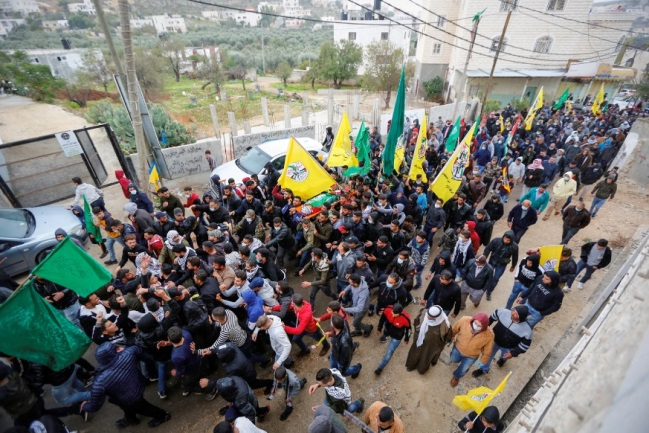 The cortège in the village of al-Mughayir. A Hamas flag was placed on the body along with the Palestinian flag (Wafa, December 5, 2020).