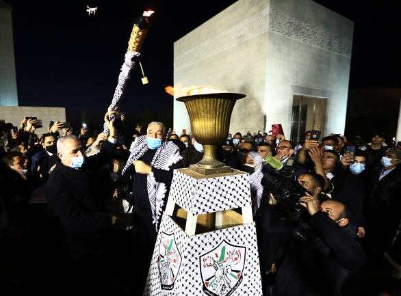 Mahmoud al-'Alul lights the traditional torch in the Muqata'a compound in Ramallah (Wafa, December 31, 2020).