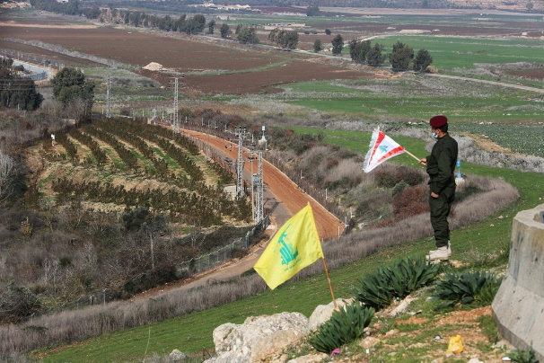 Hezbollah operative who participated in the ceremony holding a Lebanese flag.