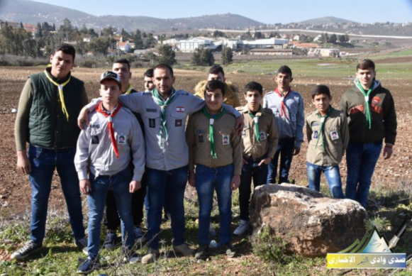 Imam al-Mahdi scouts participating in the planting campaign having their picture taken with the Israeli town of Metula in the background.