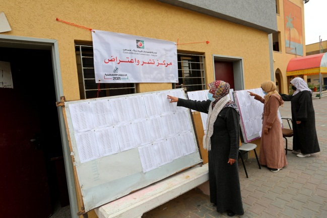Palestinian women check for their names on the updated voter registration rolls at a school in Deir al-Balah (Twitter account of photojournalist Ashraf Abu Amra, March 1, 2021).