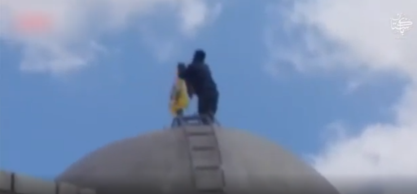 Archival clip in a video showing an Al-Fatemiyoun Brigade fighter waving the brigade flag at a mosque in Aleppo (Telegram, March 19, 2021)